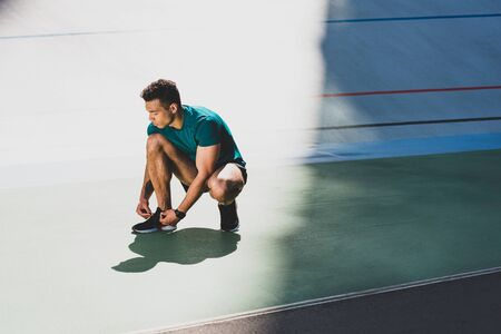 mixed race sportsman lacing up sneakers at stadium, standing on green floor