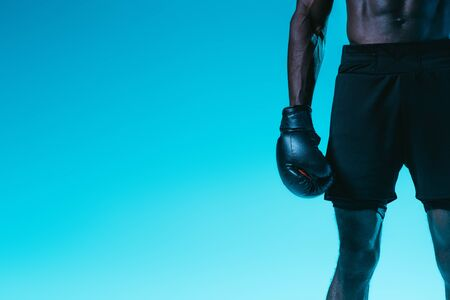 cropped view of african american boxer in shorts on blue background Archivio Fotografico - 129571815