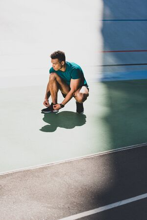 mixed race sportsman lacing up sneakers at stadium