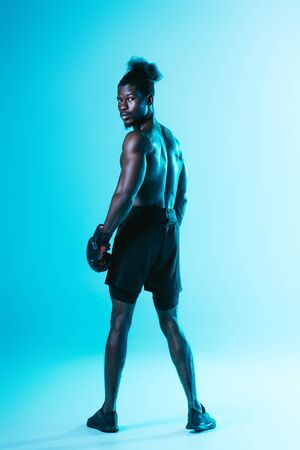 serious african american sportsman in boxing gloves looking at camera on blue background