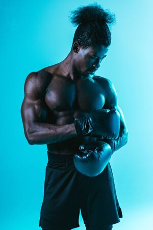 serious, muscular african american sportsman in boxing gloves posing on blue background Archivio Fotografico - 129572914