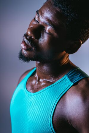 portrait of african american sportsman with sweaty face and closed eyes on grey background with lighting Banco de Imagens