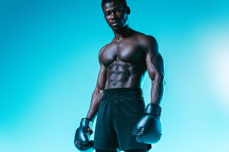 shirtless, muscular african american boxer posing at camera on blue background Archivio Fotografico - 129539330