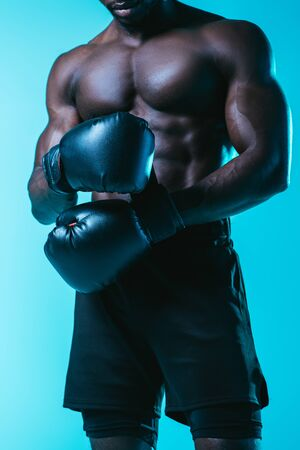 partial view of shirtless, muscular african american sportsman in boxing gloves on blue background Archivio Fotografico - 129539570