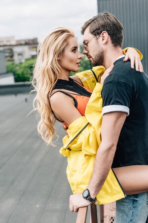 blonde woman and handsome man hugging and looking at each other