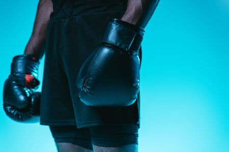 partial view of african american sportsman in shorts and boxing gloves on blue background Archivio Fotografico - 129587966