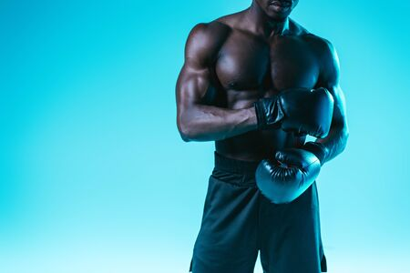 cropped view of african american boxer with muscular torso posing on blue background Archivio Fotografico - 129587968