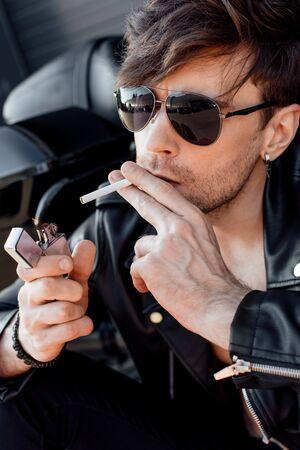 Porträtaufnahme eines jungen Mannes mit Sonnenbrille, der sich eine Zigarette anzündet, während er in der Nähe eines schwarzen neuen Motorrads sitzt Standard-Bild