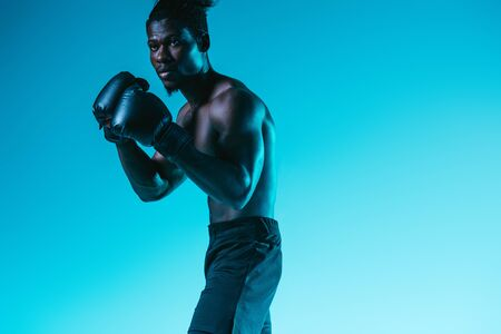 shirtless, muscular african american sportsman boxing on blue background Archivio Fotografico - 129587974