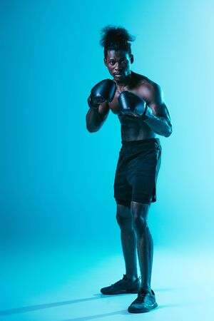 shirtless african american boxer with muscular torso looking at camera on blue background Archivio Fotografico - 129539707