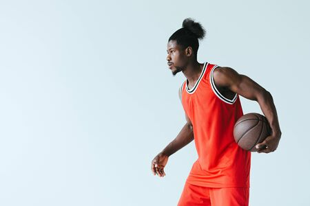 african american basketball player holding ball and looking away isolated on grey Standard-Bild