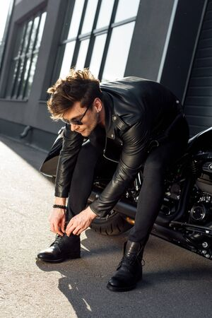 young man lacing up boots while sitting on black motorcycle