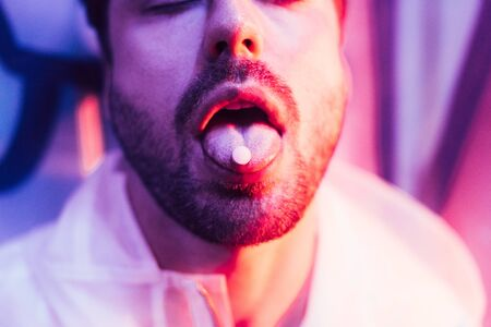 cropped view of man with closed eyes and LSD on tongue