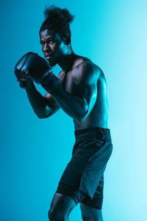 confident african american sportsman with muscular torso boxing on blue background Archivio Fotografico - 129588276