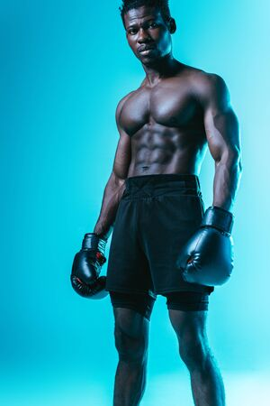 serious, muscular african american boxer looking at camera on blue background Archivio Fotografico - 129588520