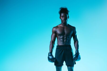 confident african american boxer with muscular torso looking at camera on blue background Archivio Fotografico - 129588807