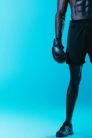 partial view of african american boxer in shorts and senakers on blue background Archivio Fotografico - 129588806