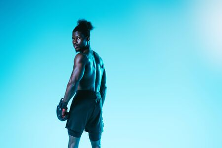 confident african american sportsman in boxing gloves looking at camera on blue background Archivio Fotografico - 129588971