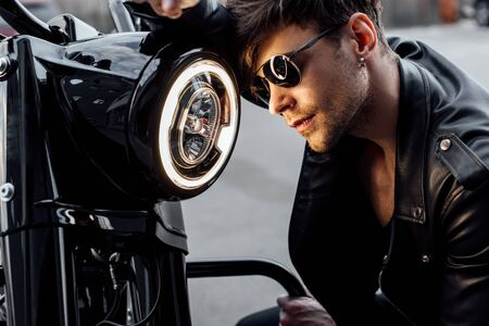 handsome young man leaning on luminous lamp on motorcycle