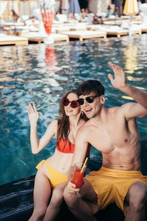 cheerful young couple looking away and waving hands while sitting at poolside Stock Photo - 130141929