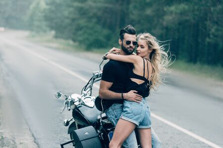 young sexy couple of motorcyclists embracing near black motorcycle on road near green forest Zdjęcie Seryjne