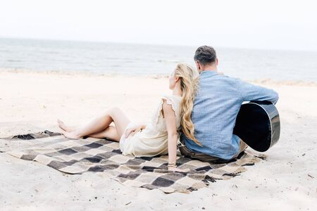 back view of young blonde barefoot woman sitting on checkered blanket near boyfriend with acoustic guitar at beach near sea 스톡 콘텐츠