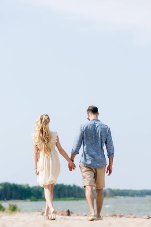 back view of adult couple walking along beach and holding hands at sunny day