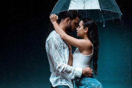 side view of attractive girlfriend hugging handsome boyfriend and holding umbrella on black 版權商用圖片