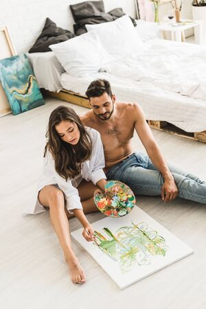 high angle view of happy couple sitting on floor while girl paiting and man looking at process Stock fotó