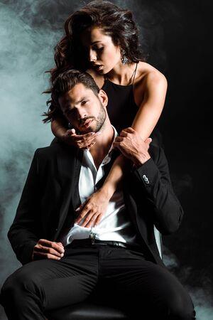 Chica apasionada de pie y abrazando a un hombre guapo con barba en negro con humo