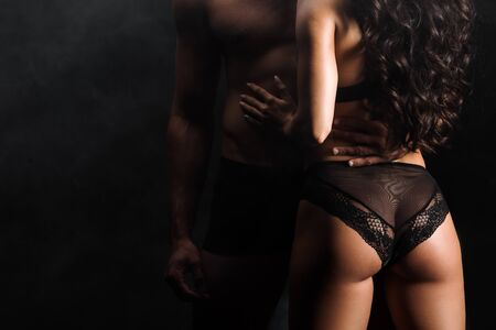 cropped view of man standing with sexy woman on black with smoke Stockfoto
