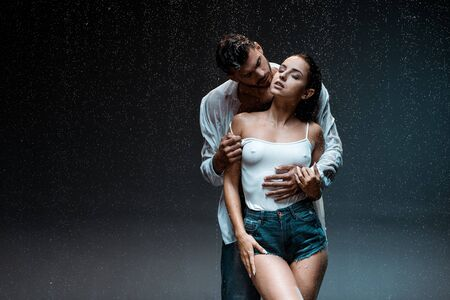handsome man standing with sexy and wet girlfriend with closed eyes under raindrops on black Reklamní fotografie