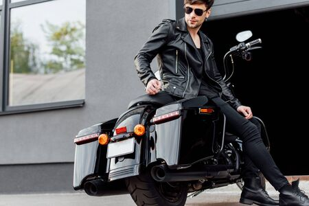 handsome motorcyclist in sunglasses and leather jacket sitting on motorcycle near opened garage