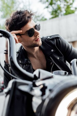 selective focus of handsome man in sunglasses sitting on motorcycle and looking away Stock Photo