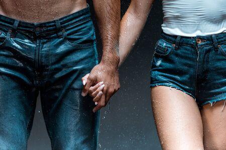 bijgesneden weergave van natte man hand in hand met meisje in denim shorts op zwart