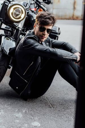 handsome young man sitting on asphalt near motorcycle