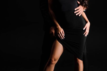 cropped view of man hugging girl in dress standing isolated on black Stock Photo