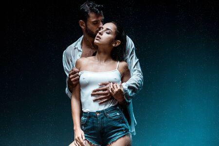 bel homme debout et embrassant sa petite amie avec les yeux fermés sous les gouttes de pluie sur fond noir