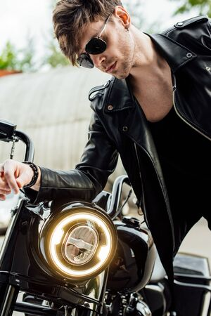 handsome man in leather jacket leaning on handlebars of motorcycle
