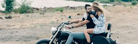 young couple of bikers hugging on black motorcycle at sandy beach near river, panoramic shot
