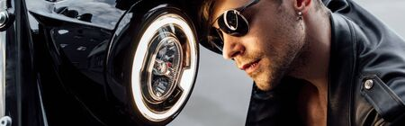 panoramic shot of handsome man in sunglasses near lamp on Stock Photo