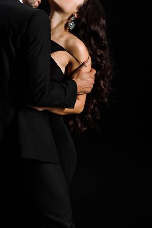 cropped view of man undressing woman isolated on black