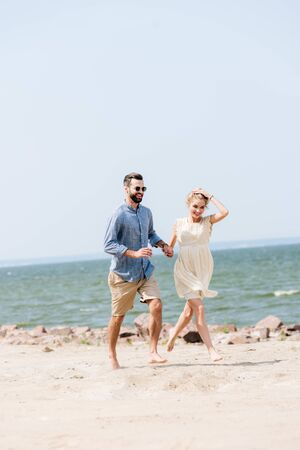 happy young couple holding hands while running along beach
