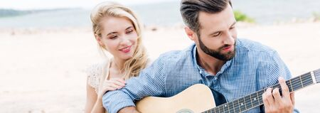 smiling beautiful young woman sitting near boyfriend with acoustic guitar at beach near sea, panoramic shot