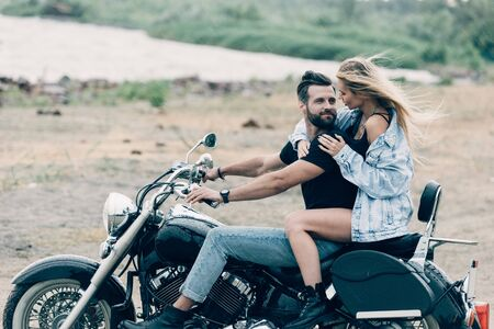 young smiling couple of bikers sitting on black motorcycle at beach near river