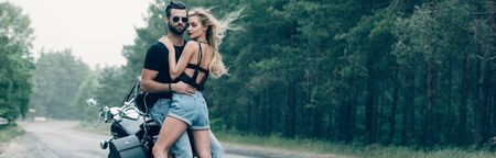 young sexy couple of motorcyclists embracing near black motorcycle on road near green forest, panoramic shot