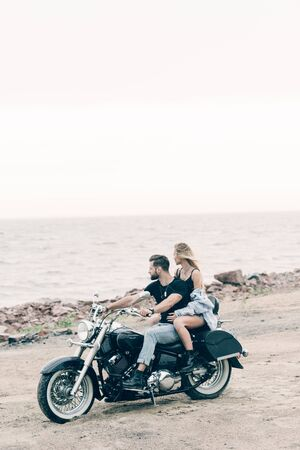 young couple of bikers on black motorcycle near river