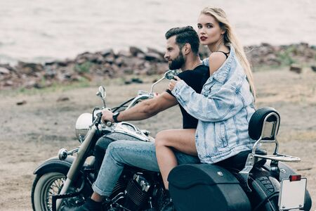 couple of bikers sitting on black motorcycle at beach near river