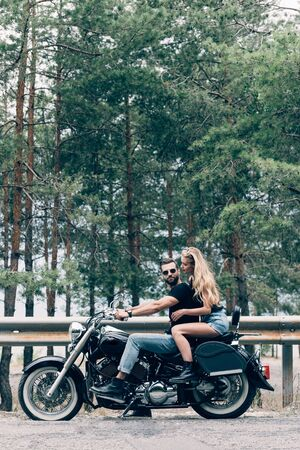 side view of young couple of bikers on black motorcycle on road near green forest