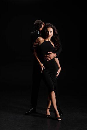 man hugging happy woman in dress standing on black